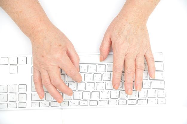 Mains d'une vieille femme en tapant sur le clavier, isolé sur blanc, gros plan.