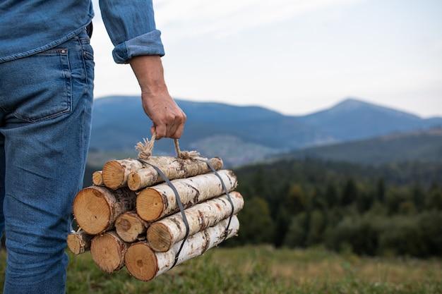 Mains de voyageur homme tenant du bois de chauffage pour le feu dans les montagnes. place pour l'inscription.
