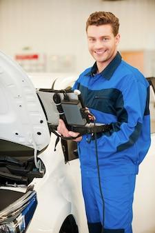 Maintenant je connais le problème. jeune homme confiant travaillant sur un ordinateur portable spécial et souriant en se tenant debout dans un atelier près d'une voiture