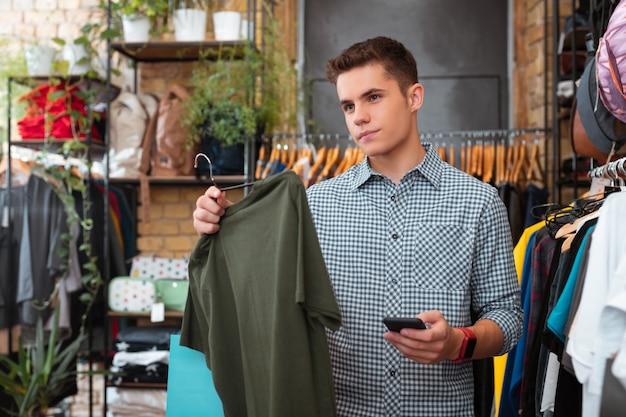 Maintenant mauvais. calme jeune tenant un t-shirt vert dans un magasin de vêtements et en pensant au prix de celui-ci