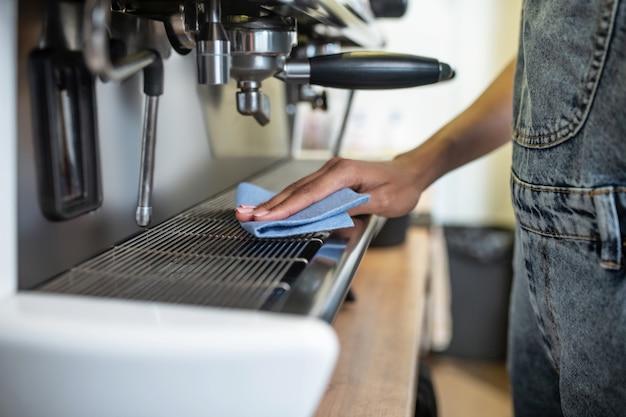 Maintenir la propreté. surface de lavage des mains des femmes de la machine à café touchant la serviette en lieu de travail de café