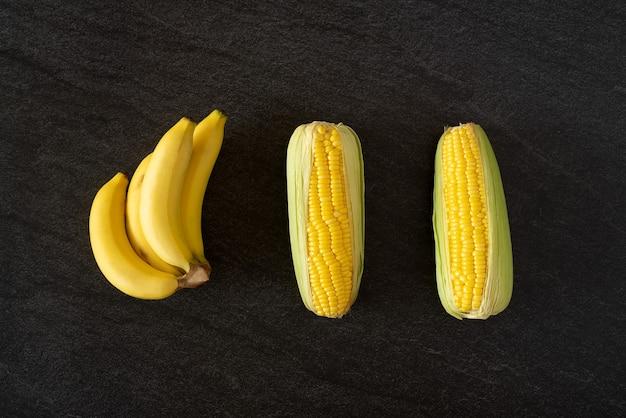 Maïs bananaraw juteux frais sur fond noir en pierre