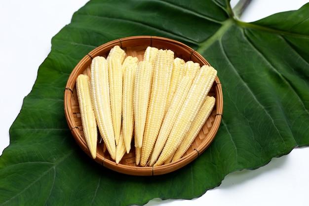 Maïs de bébé dans le panier en bambou sur la feuille de taro