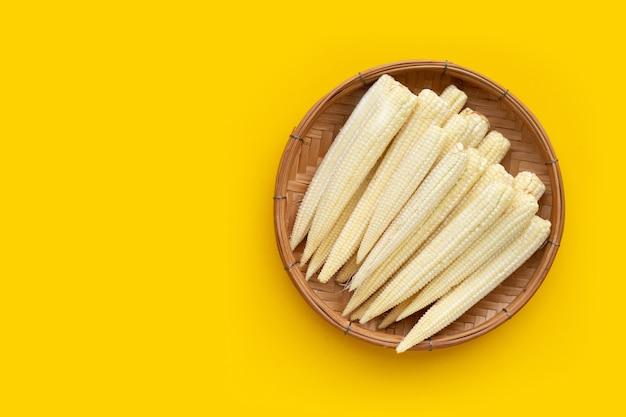 Maïs bébé dans un panier en bambou sur fond blanc.