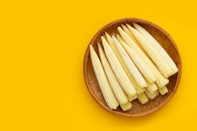 Maïs bébé dans un panier en bambou sur fond jaune.