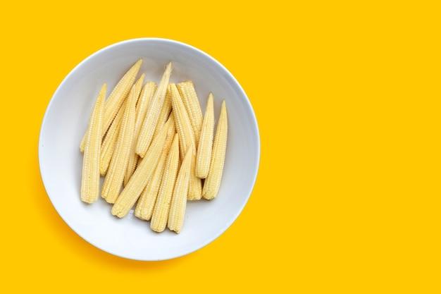 Maïs bébé en plaque blanche sur fond jaune.