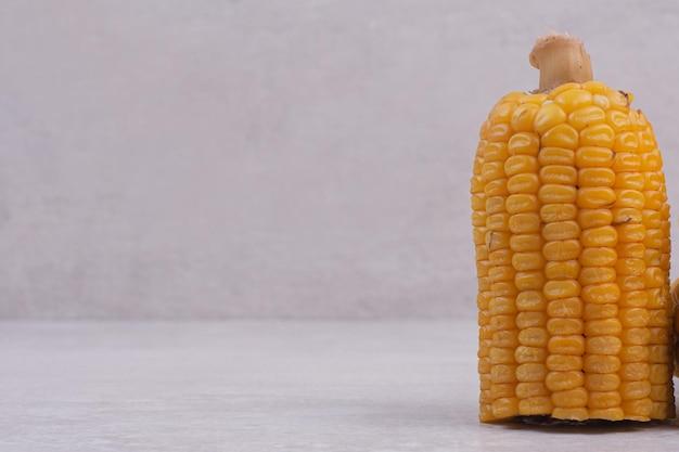 Maïs bouilli à moitié coupé sur une table blanche.