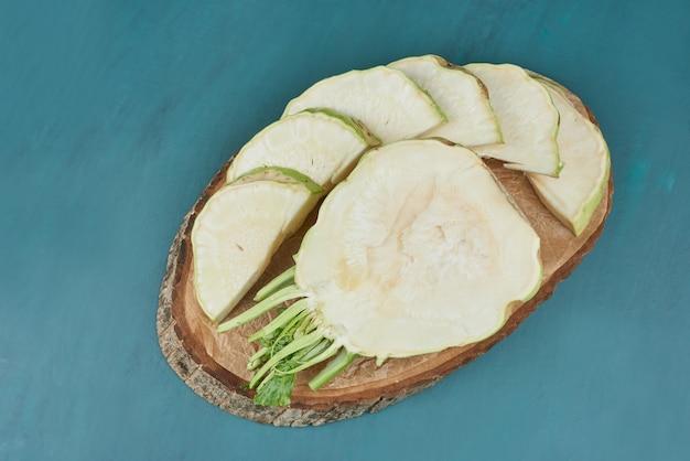 Maïs de céleri sur bleu sur un morceau de bois.