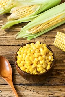 Maïs en conserve dans une assiette en bois et des épis de maïs frais sur un fond en bois rustique
