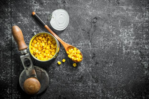 Maïs en conserve dans une boîte de conserve et une cuillère. sur rustique foncé
