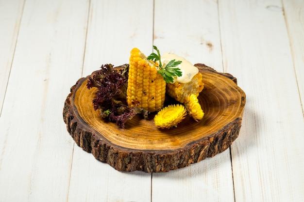 Maïs coupé cuit avec du beurre sur la planche de bois