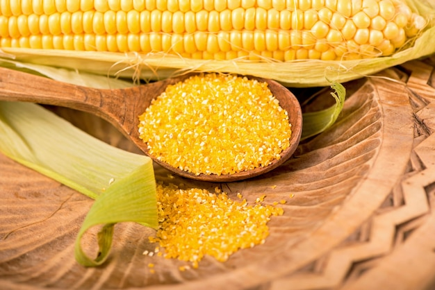 Maïs cru avec des feuilles vertes sur fond blanc.