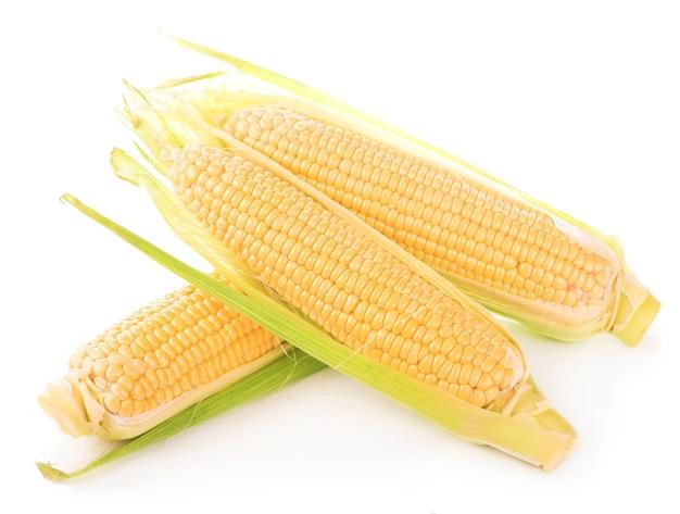 Maïs cru avec des feuilles vertes sur une surface blanche