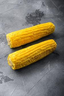 Maïs doux jaune biologique en épi, sur table texturée grise, vue latérale.