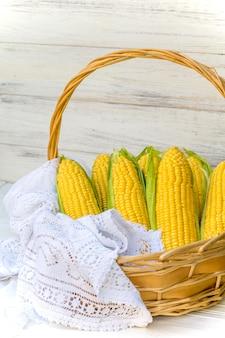 Maïs frais en épi dans un panier en osier. épis de maïs non traités. légumes de maïs frais dans le panier. maïs récolté dans le panier en osier, épis de maïs fraîchement cueillis dans le paysage de champ agricole, sélective