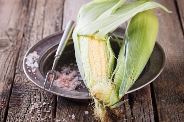 Maïs frais en épi sur des plateaux vintage au sel de l'himalaya