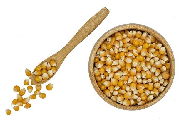 Maïs-grain dans un bol en bois avec cuillère isolé sur fond blanc