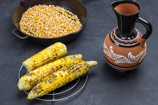 Maïs grillé, poêle à maïs et cruche en céramique. fond noir. vue de dessus