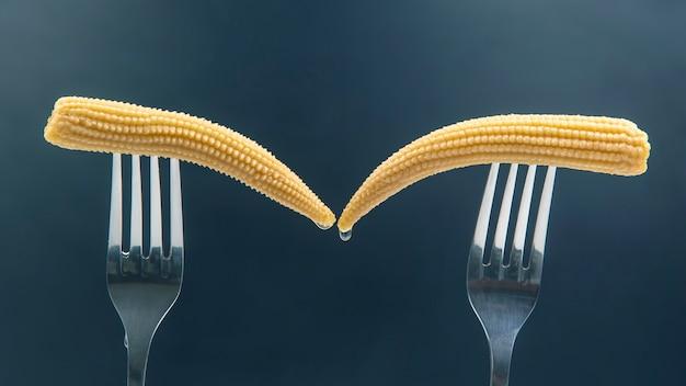 Maïs mariné sur une fourche gros plan sur un fond sombre. nourriture et légumes