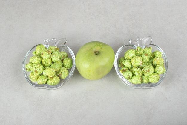 Maïs soufflé aromatisé rempli dans un porte-bonbons en forme de pomme avec une pomme verte au milieu sur du marbre.