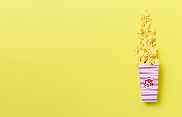 Maïs soufflé au beurre en boîte sur fond jaune