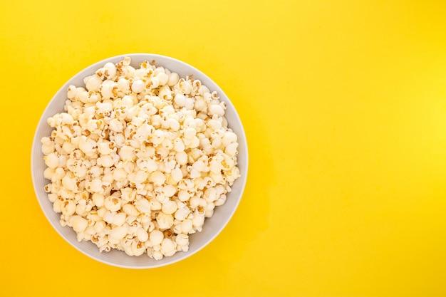 Maïs soufflé au beurre dans une tasse de pop-corn rouge, collation à la maison ou au cinéma