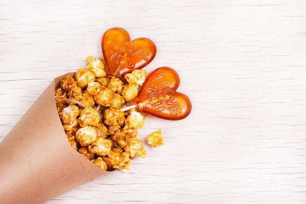 Maïs soufflé au caramel doré dans une tasse en papier et des sucettes en forme de cœur.
