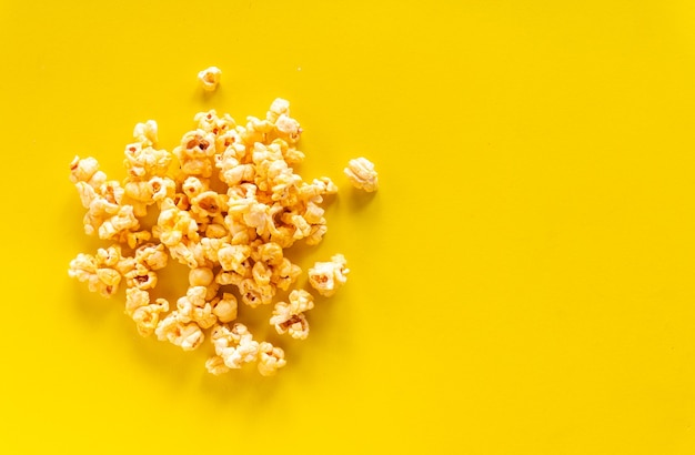 Maïs soufflé au caramel sur fond jaune avec espace copie