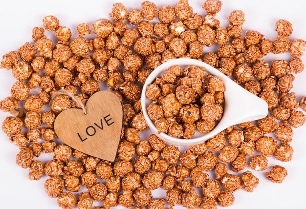Maïs soufflé au chocolat et au caramel dans une tasse blanche et un cœur en bois