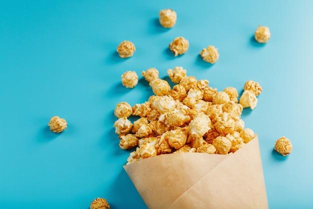 Maïs soufflé au glaçage au caramel dans une enveloppe en papier sur fond bleu.