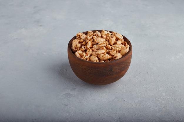 Maïs soufflé de blé dans un bol en bois sur fond de pierre au centre.