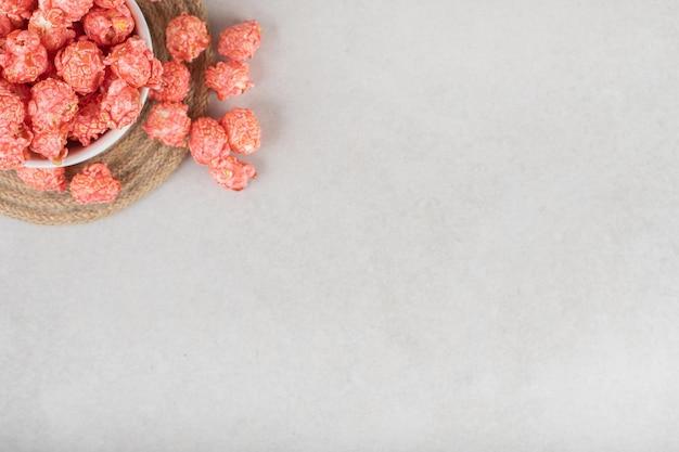 Maïs soufflé confit dans une tasse et sur un dessous de plat sur une table en marbre.