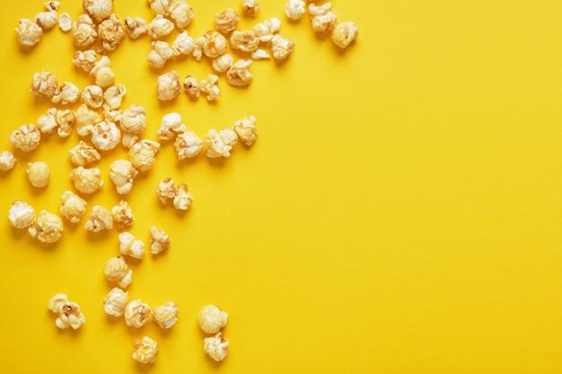 Maïs soufflé sur fond jaune. modèle de pop-corn. vue de dessus, espace copie