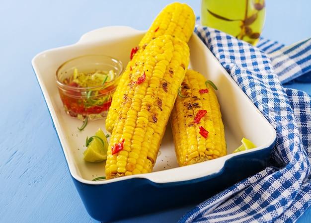 Maïs sucré grillé avec sauce mexicaine, piment et citron vert sur fond bleu.