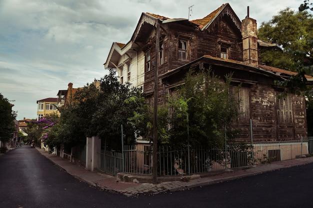 Maison abandonnée aux vitres brisées au centre d'une ville.