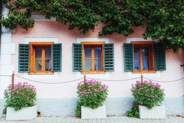Maison alpine autrichienne typique avec des fleurs aux couleurs vives sur le balcon