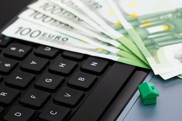 Maison et argent sur clavier d'ordinateur portable
