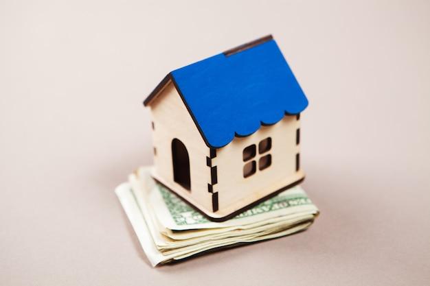 Maison sur des billets d'un dollar sur la table, concept de dépenses de maison