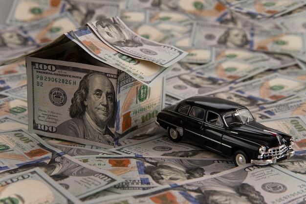 Une maison de billets d'un dollar et une voiture sur des billets éparpillés