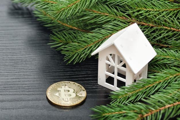 Maison blanche sur une branche de sapin vert et pièce de monnaie bitcoin