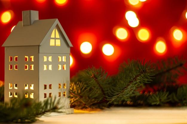 Maison blanche avec des branches d'arbres de noël sur table blanche et bokeh sur fond rouge. joyeux noël et bonne année. copier l'espace