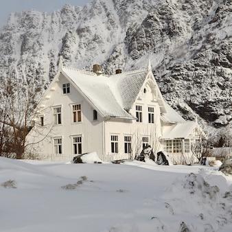 Maison blanche enneigée dans les montagnes
