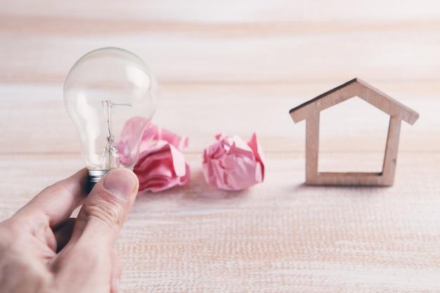 Maison en bois avec ampoule sur la table, un symbole pour la construction, idée créative de l'ampoule