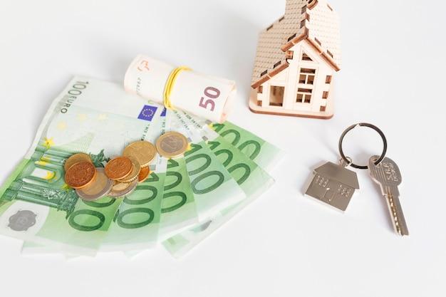 Maison en bois et argent comptant sur la table