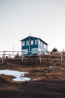 Maison en bois blanc et bleu sur champ brun sous ciel blanc pendant la journée