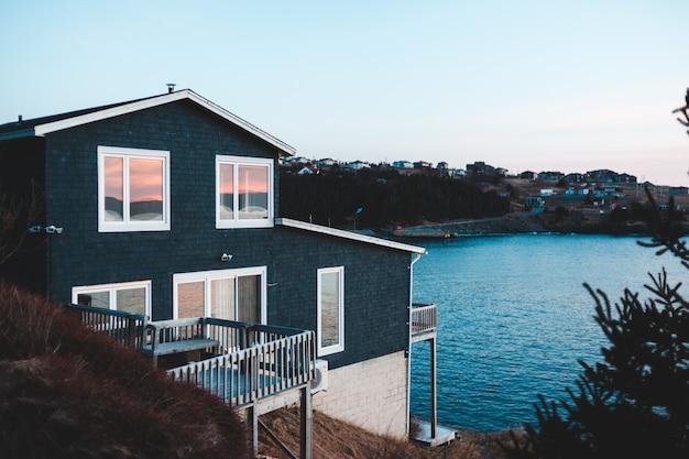 Maison en bois bleu et blanc près d'un plan d'eau pendant la journée
