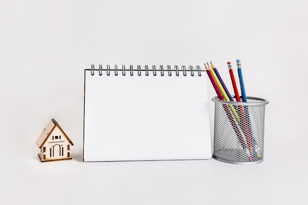 Maison en bois, bloc-notes et crayon en surface blanche