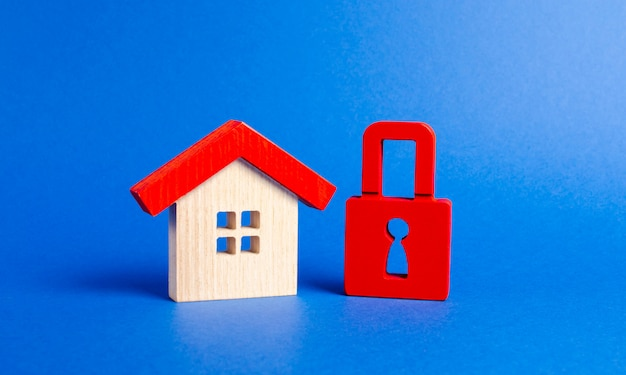 Une maison en bois et un cadenas rouge.