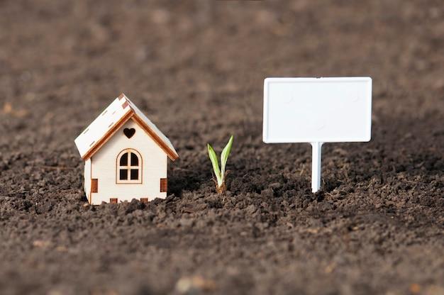 Une maison en bois avec un cœur et un panneau blanc vierge à côté sur le terrain