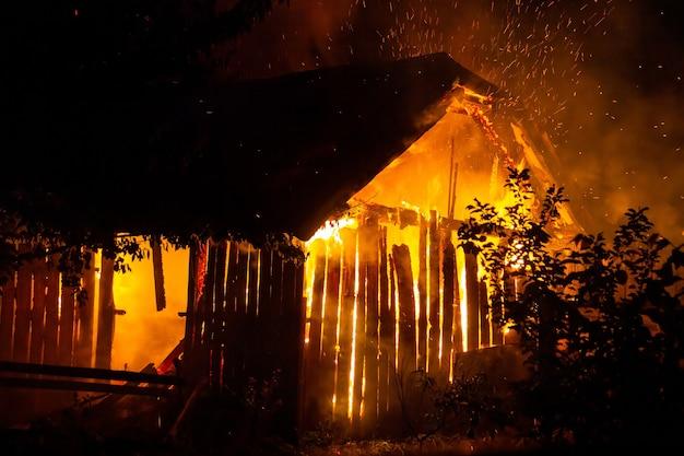 Maison en bois ou grange en feu la nuit